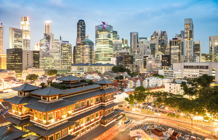 High view of Singapore skyline with skyscrapers and Tooth Relic Temple at blue hour - World famous top south east Asia destinations - City panorama on vivid warm filter with nightscape color tones Imagens - 75213980