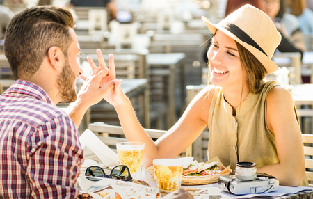 Couple in love having fun at beer bar on travel excursion - Young happy tourists enjoying happy moment at street food restaurant - Relationship concept with focus on girl face on warm bright filter
