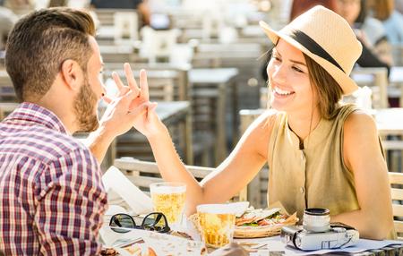 Pareja de enamorados que se divierten en el bar de cerveza en la excursión de viajes - Jóvenes turistas felices disfrutando de momento feliz en el restaurante de comida callejera - Concepto de relación con el foco en la cara de la niña en el cálido filtro brillante