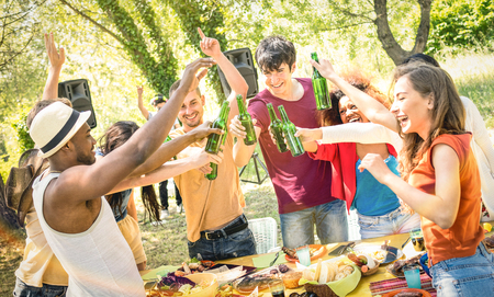 Young multiracial friends toasting beer at barbecue garden party - Friendship concept with happy people having fun at backyard summer camp - Food and drinks fancy dinner with dj music set outdoors