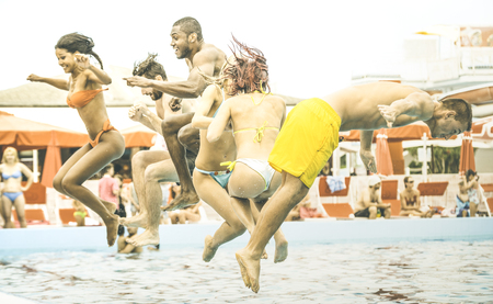 Side view of multiracial friends jumping at swimming pool party - Vacation concept with happy guys and girls having fun in summer day at leisure aquapark - Active young people on retro contrast filter Stock Photo