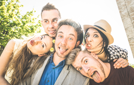 Group of best friends taking selfie outdoor with back lighting - Happy concept with young people having fun together - Cheer and friendship at city tour - Retro vintage filter with focus on middle guy Reklamní fotografie - 75689822