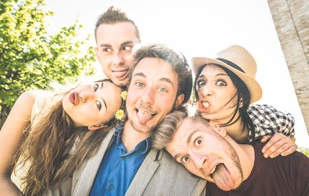 Gruppe der besten Freunde selfie im Freien mit Hintergrundbeleuchtung nehmen - Happy-Konzepts mit jungen Menschen Spaß zusammen - Cheer und Freundschaft bei Stadtrundfahrt - Retro Vintage-Filter mit Fokus auf Mitte Kerl Standard-Bild - 75689822