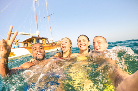 Young multiracial friends taking selfie and swimming on sailing boat sea trip - Rich happy guys and girls having fun in summer party day - Exclusive vacation concept - Bright afternoon  warm filter