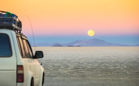 incahuasi: Full moon sunset with off road jeep vehicle on Salar De Uyuni - World famous nature wonder place in Bolivia - Travel and wanderlust concept in South American exclusive landscape - Focus on infinity