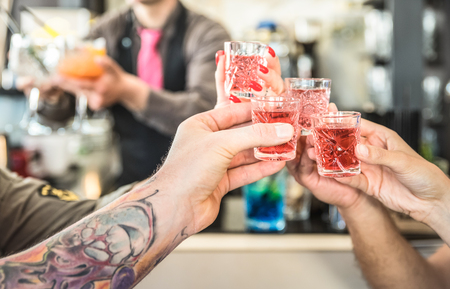 Group of drunk friends toasting cocktails at bar restautant - Food and beverage concept on nightlife moments - Defocused bartender serving drinks on background - Focus on hands cheering red shot glass