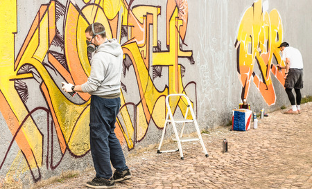 Urban street artists painting colorful graffiti on generic wall - Modern art concept with guys performing live murales with aerosol color spray - Focus on left person - Warm neutral filter Stock Photo