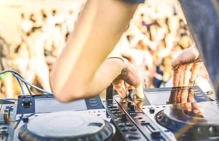 Close up of dj playing electro sound on modern cd usb player at summer beach party - Music festival and entertainment concept  - Defocused background with shallow depth of field - Focus on mixing hand Stock Photo - 78679168