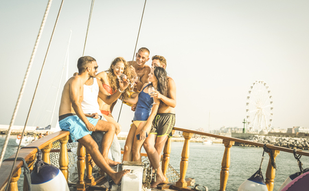 Happy multiracial friends having fun drinking wine at sail boat trip party - Friendship concept with young multi racial people on sailboat - Travel lifestyle on exclusive location - Warm retro filter Stock Photo
