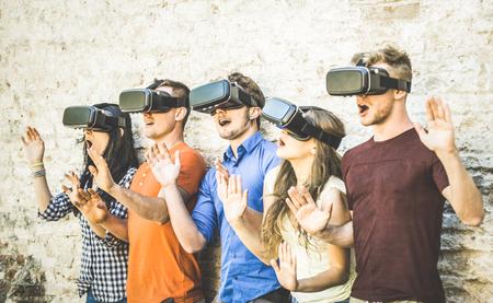 Gruppo di amici che giocano su vetri vr all'aperto - Realità virtuale e concetto tecnologico indossabile con i giovani divertirsi insieme a occhiali da cuffia - Trend di generazione digitale - Retro contrasto filtro Archivio Fotografico - 78689782