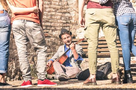 Jonge mensen kijken naar straatkunstenaar die een akoestische klassieke gitaar speelt in het buitenland - Avontuur levensstijl concept met muzikant man die geld verdienen met artistieke vaardigheden - Filmpjes van de warme middag
