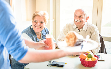 Waiter serving senior couple eating at vegan restaurant - Retired man and woman on active elderly having fun - Happy retirement concept with mature people together - Bright filter with focus on lady