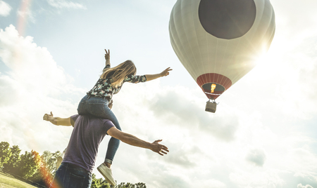 Happy couple in love on honeymoon vacation cheering at hot air balloon - Summer travel concept with young people travelers having fun at trip excursion - Vintage contrast retro filter with backlight Archivio Fotografico