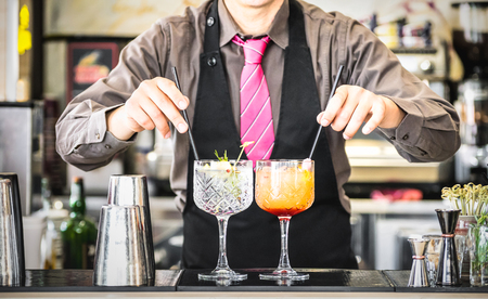 Classic bartender serving gin tonic and tequila sunrise with straw on drink glasses cups at fashion cocktail bar - Food and beverage concept with professional barman working at mixology restaurant Stockfoto