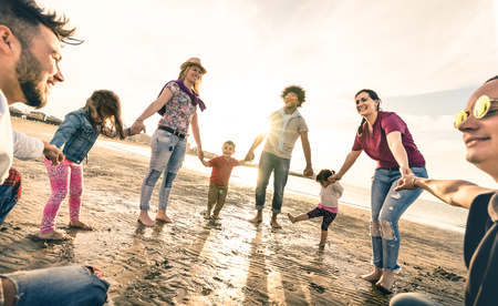 Happy multiracial families round dancing at the beach on ring around the rosy style - Multicultural happiness joy concept with mixed race people having fun outdoor at sunset - Vintage backlight filter