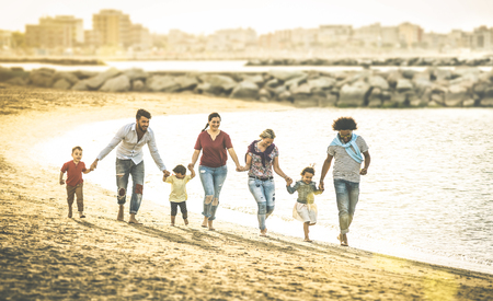 Happy multiracial families running together at beach holding hands on vacation - Multicultural summer joy concept with mixed race people having fun outdoor at sunset - Warm vintage backlight filter 스톡 콘텐츠