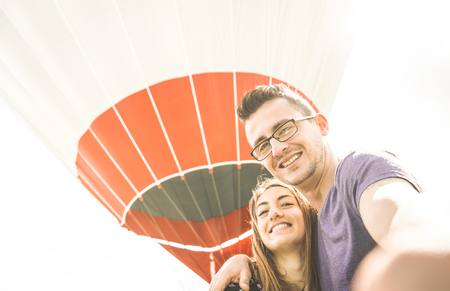 Happy couple in love on honeymoon vacation taking selfie at hot air balloon - Summer travel concept with young people travelers having fun at excursion - Vintage contrast retro filter with backlight 版權商用圖片