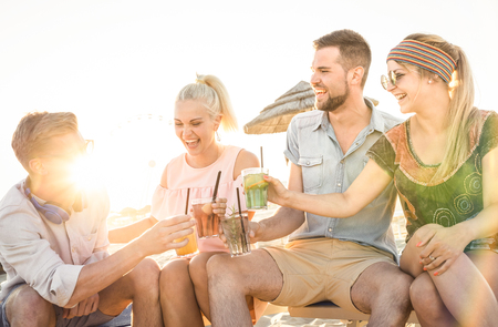 Happy friends group having fun at beach party drinking cocktail at sunset - Summer joy and friendship concept with young people on vacation - Warm sunshine filtered color tone with focus on blond girl Stock Photo