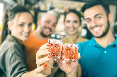 Defocused Bokeh von den betrunkenen Freunden, die Cocktailschützen an der Bar rösten - Nahrungsmittel- und Getränkekonzept auf Nachtleben-Geburtstagsfeier - Konzentrieren Sie sich auf Hände, die rote Schnapsglasgetränke zujubeln - Knickente und orange Filter Standard-Bild