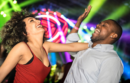 Multiracial young couple dancing at night club with laser light show - Happy people having crazy fun at nightclub after party - Nightlife drunk concept with guy and girl celebrate at concert festival