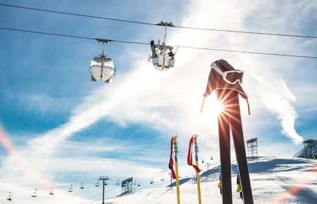 Skiing goggles and skis poles at resort glacier with chair lift on french alps - Winter vacation travel concept - High season opening on mountain slopes - Focus on sport equipment - Backlight contrast