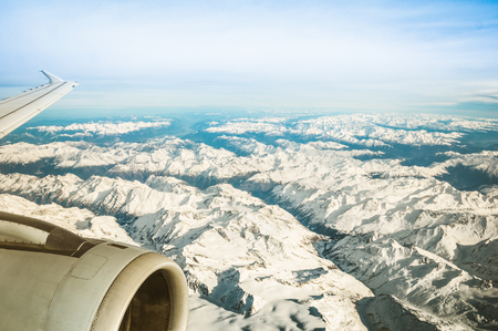 Aerial view of European Alps with misty horizon and part of airplane wing engine - Travel concept and winter vacation on white snow mountains - Trip wander to exclusive luxury destinations worldwide Stock fotó