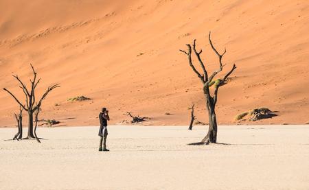Eenzame avontuurlijke reisfotograaf bij de Deadvlei-krater in het Sossusvlei-gebied - Namibische wereldberoemde woestijn - Wandel concept met Afrikaanse natuurwonder met uniek wild landschap in Namibië