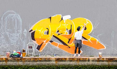 Straßenkünstler, der farbige Graffiti auf Wand des öffentlichen Raumes malt - Konzept der modernen Kunst des städtischen Kerls Live-murales-Farbe mit gelbem Aerosolfarbspray - bewölkter Nachmittag Filter ausführend und vorbereitend Standard-Bild