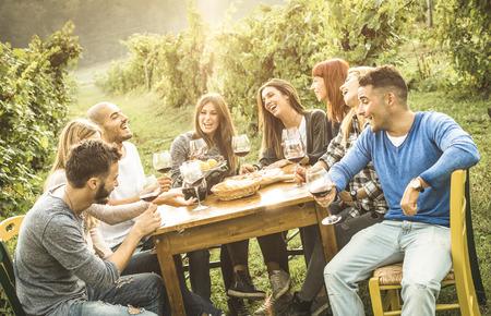 Glückliche Freunde, die trinkenden Rotwein des Spaßes im Freien haben - junge Leute, die Lebensmittel zur Erntezeit in der Bauernhausweinbergweinkellerei essen - Jugendfreundschaftskonzept mit flacher Schärfentiefe - warmer Kontrastfilter