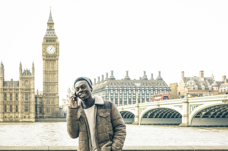 African american young man using mobile smart phone at Thames riverbank in London - Hipster guy male model with modern cell smartphone wearing trendy fashion clothes - Bright desaturated filter