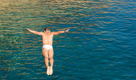 Cliff diver guy jumping in the blue sea from high rocks wall - Joyful freedom concept and carefree sensation feeling the pure connection with the nature - Natural vivid afternoon color tones Stock Photo