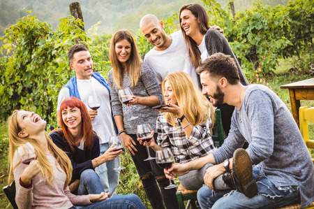 Happy friends having fun outdoor - Young people drinking red wine at harvest time in farmhouse vineyard winery - Youth friendship concept with mates using smartphone for a live mobile phone call Stock Photo - 89223671