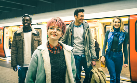 Multiracial hipster friends group walking at tube subway station - Urban friendship concept with young people having fun in city underground area - Teal and orange filter with focus on pink hair girl