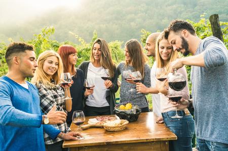 Gruppe glückliche Freunde, die den Spaß draußen trinkt Rotwein - junge Leute essen lokales neues Lebensmittel an der Traubenernte in der Bauernhausweinbergweinkellerei haben - Jugendfreundschaftskonzept auf einem klaren warmen Filter