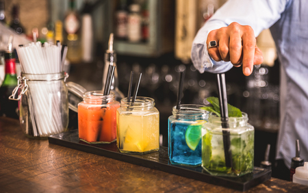 Bartender hand at multicolored fashion drink with straw on vintage glass cups in fashion cocktail bar - Food and beverage concept with professional barman working at mixology restaurant - Vivid colors 스톡 콘텐츠