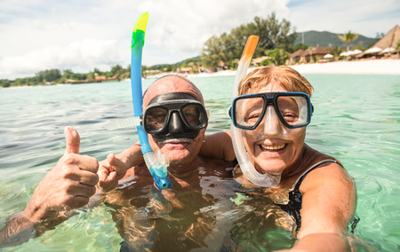 Senior happy couple taking selfie in tropical sea excursion with water camera - Boat trip snorkeling in exotic scenarios - Active retired elderly and fun concept around the world - Warm bright filter Stockfoto