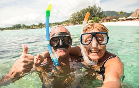 Senior happy couple taking selfie in tropical sea excursion with water camera - Boat trip snorkeling in exotic scenarios - Active retired elderly and fun concept around the world - Warm bright filter Foto de archivo