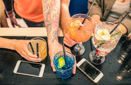 友人のグループは、ファッションバーのレストランでカクテルを飲む-モバイルスマートフォン上の人々の手の高い角度のビューポイント-酔った男と