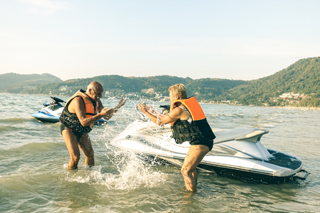Senior happy couple having playful fun at jet ski on beach island hopping tour - Active elderly travel concept around the world with retired people riding water scooter jetski - Bright vintage filter Stock Photo