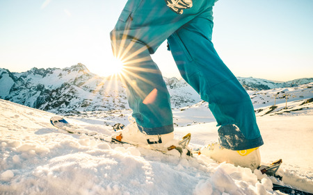 Benen van professionele skiër bij zonsondergang op relaxmoment in skigebied Franse Alpen - Wintersportconcept met avontuurlijke kerel op bergtop klaar om naar beneden te rijden - Zijaanzichtpunt met azuurblauwe vintage filter