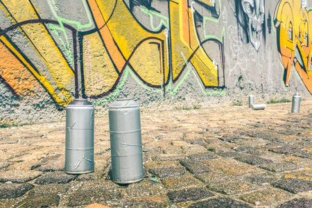 Detail of aerosol spray can at colorful graffiti on wall - Modern street art concept with urban painting perform and murales live preparation - Bright vintage retro filter Stock Photo