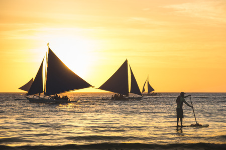 Silhouette of sailing boats at sunset in Boracay island - Unrecognizable man with paddle surfing - Exclusive travel destination in Philippines - Warm vintage filtered look - Focus in foreground