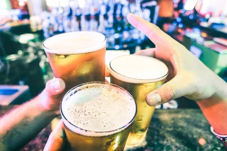 カクテルバーでビールパイントを乾杯する友人の手 - 醸造所のパーティークラブで楽しんでいる人々との友情の概念 - 一緒に食べ物や飲み物の派手