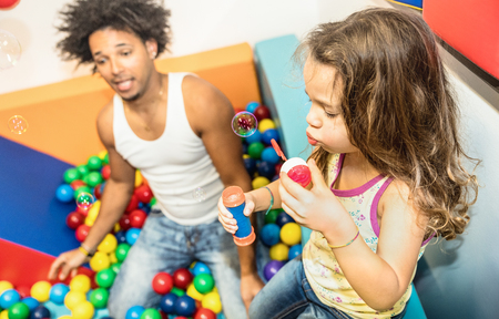 Latin american dad playing with mixed race daughter on ball pit pool at kindergarten playroom - Family concept with happy multiracial child and father having fun at kid toyroom with soap bubble blower