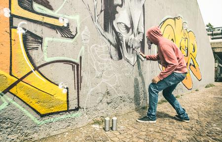 Artista de la calle pintando graffiti colorido en la pared genérica - Concepto de arte moderno con chico urbano realizando y preparando murales en vivo con aerosol de aerosol de varios colores - Filtro retro contraste vintage Foto de archivo