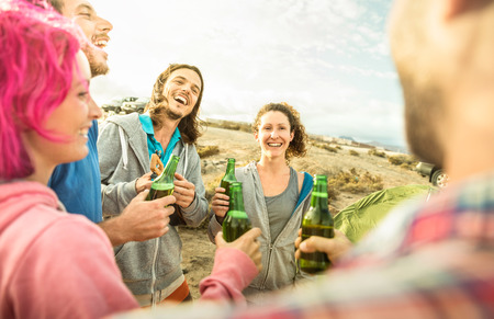 Hipster friends having fun together at beach camping party - Friendship travel concept with young people travelers playing ukulele and drinking bottled beer at summer surf camp - Warm bright filter