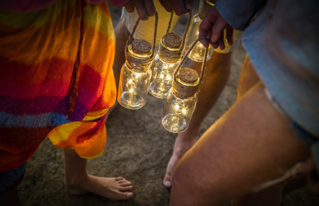 Hipster friends having fun together at beach camping party - Friendship travel concept with young people holding neon led lanterns at summer sea camp - High iso image with night dark vignetting filter