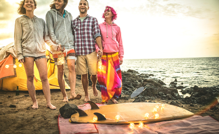 Hipster friends having fun walking with led neon lanterns at beach camping party - Friendship travel concept with young wanderer people relaxing at sunset on summer surf camp - Warm dark retro filter
