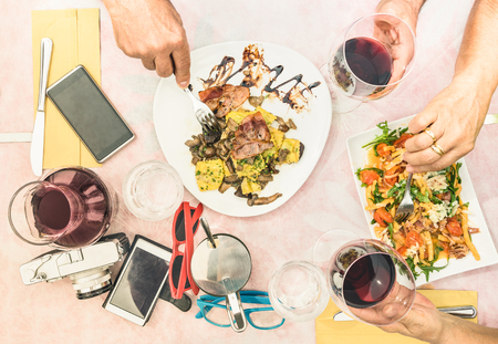 Top view of senior couple hands eating food and drinking wine at fashion restaurant - Retired people enjoying ravioli pasta and seasonal salad at travel break - Lunch and dinner concept outdoors