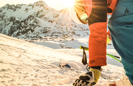 Professional skier at sunset touching snow on relax moment in french alps ski resort - Winter sport concept with adventure guy on mountain top ready to ride - Side view point with warm sunshine filter Stock Photo